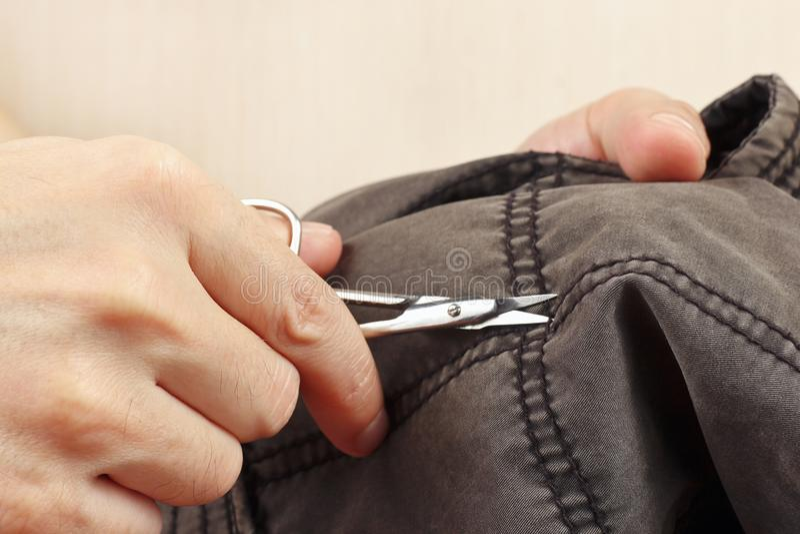 Ręki sukiennik z parą nożyce bawełny rżnięci ubrania zamykają up obraz stock