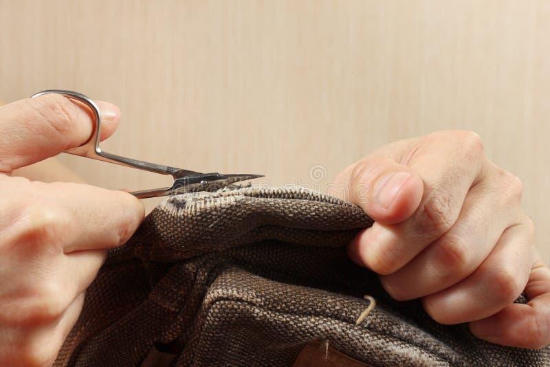 Ręki sukiennik z parą nożyce cięcia płótna silny zakończenie up zdjęcie royalty free