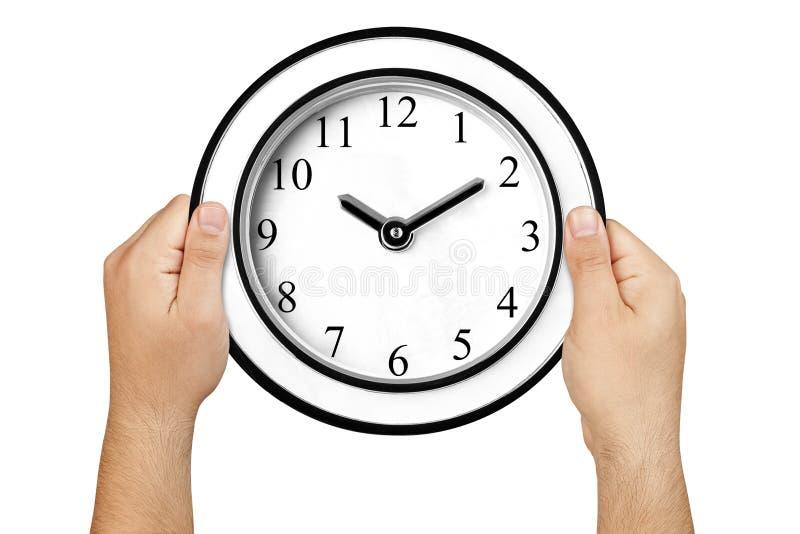 Ręki trzyma ściennego zegar odizolowywający obrazy royalty free