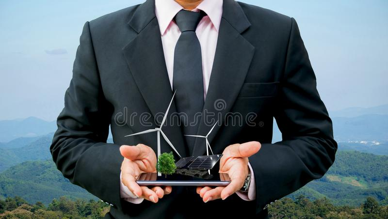 Ręki trzyma biznesmena na drzewnym czystym silniku wiatrowym smartphone elektrycznej energii ogniwie słonecznym i przyszłość obrazy stock