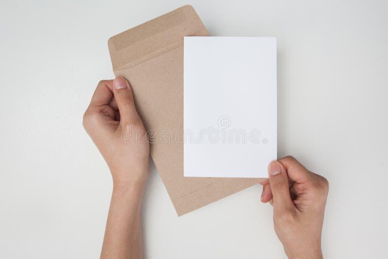 Ręki trzyma brown kopertę z pustym papierem na białym backgro obraz royalty free