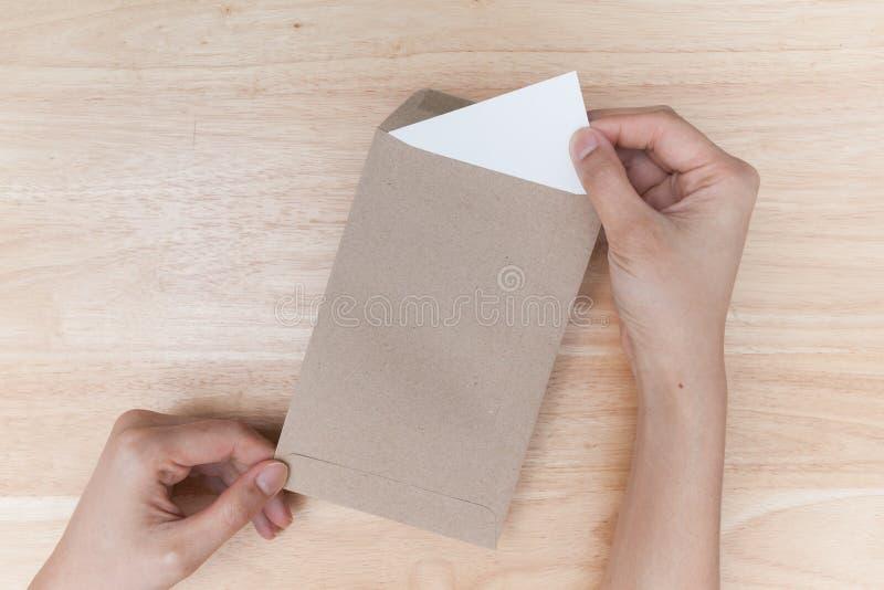 Ręki trzyma brown kopertę z pustym papierem na drewnianym backgrou fotografia stock