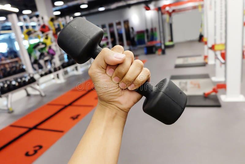 Ręki trzyma dumbbells w sporta klubie zdjęcia stock