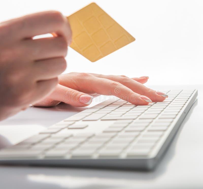 Ręki trzyma kartę kredytową i używa komputer dla online zakupy zdjęcia stock