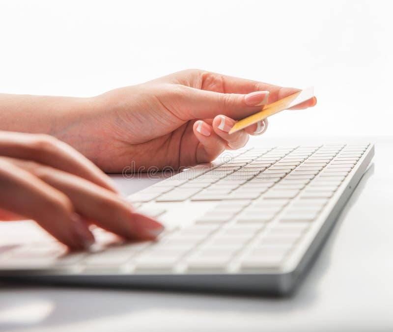 Ręki trzyma kartę kredytową i używa laptop dla online zakupy zdjęcia stock