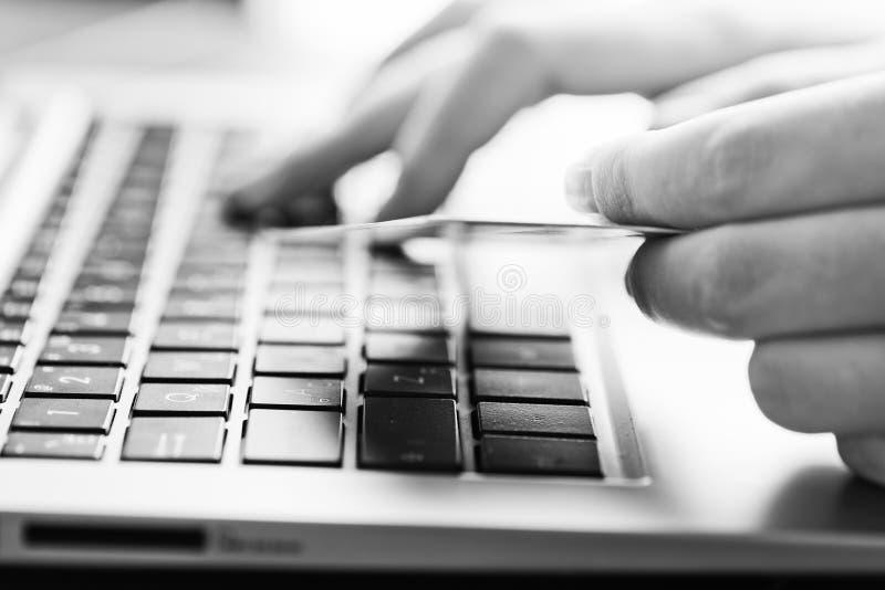 Ręki trzyma kredytową kartę i używa laptop obraz stock