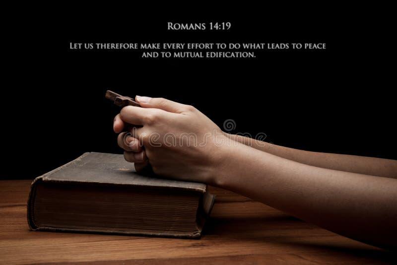 Ręki trzyma krzyż na świętej biblii z wersetem fotografia royalty free