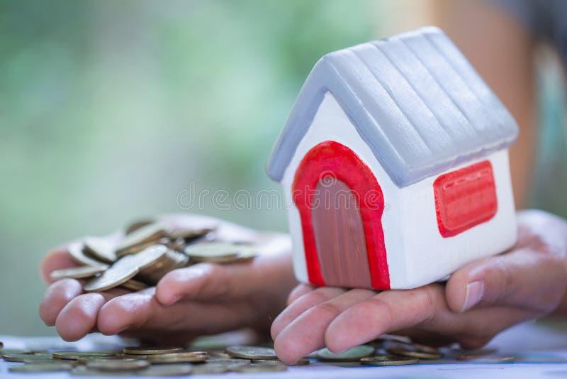 Ręki trzyma monety i mieścą hipoteki plan i mieszkaniową podatku oszczędzania strategię wzorcowego, Lokalowego, hipoteka, inwesty zdjęcia royalty free