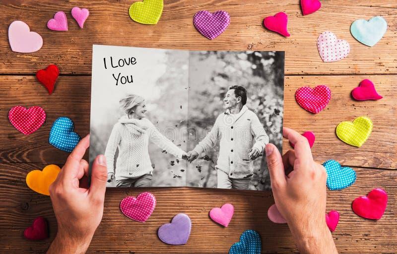 Ręki trzyma obrazek starsza para, kolorowi serca studio zdjęcie royalty free