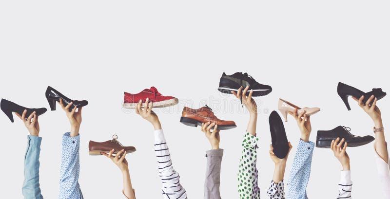 Ręki trzyma różnych buty na odosobnionym tle obraz royalty free