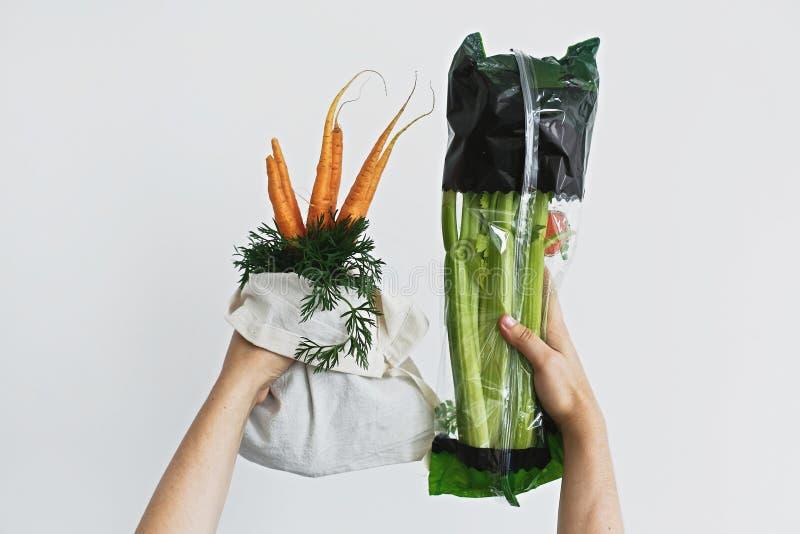 R?ki trzyma reusable eco ?yczliw? torb? z ?wie?ymi marchewkami przeciw selerowi w celofanowym plastikowym pakunku na bia?ym tle z zdjęcie stock