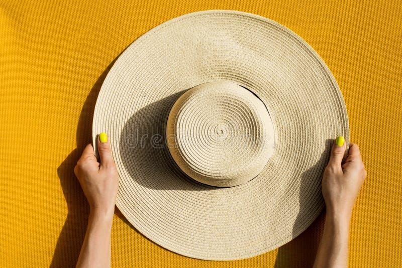 Ręki trzyma słomianego kapelusz na wibrującym żółtym backgrou młoda dziewczyna obrazy royalty free