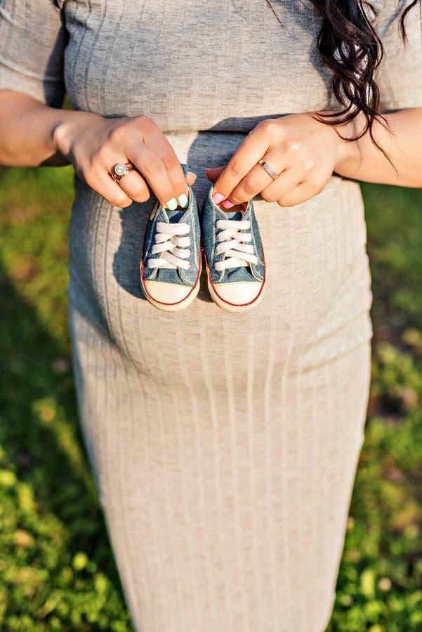 Ręki trzyma sneakers dla nowonarodzonego fotografia royalty free