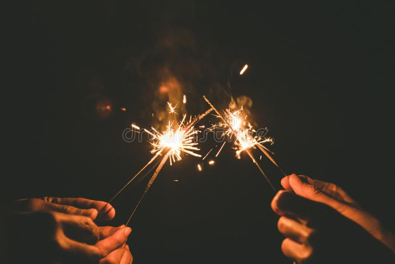 Ręki trzyma sparklers dla świętują w nighttime obraz stock