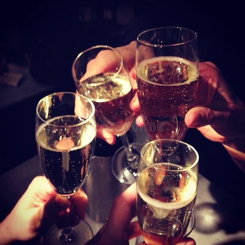 ręki trzyma szampańskich fletowych szkła cztery wznoszą toast clinking obrazy stock