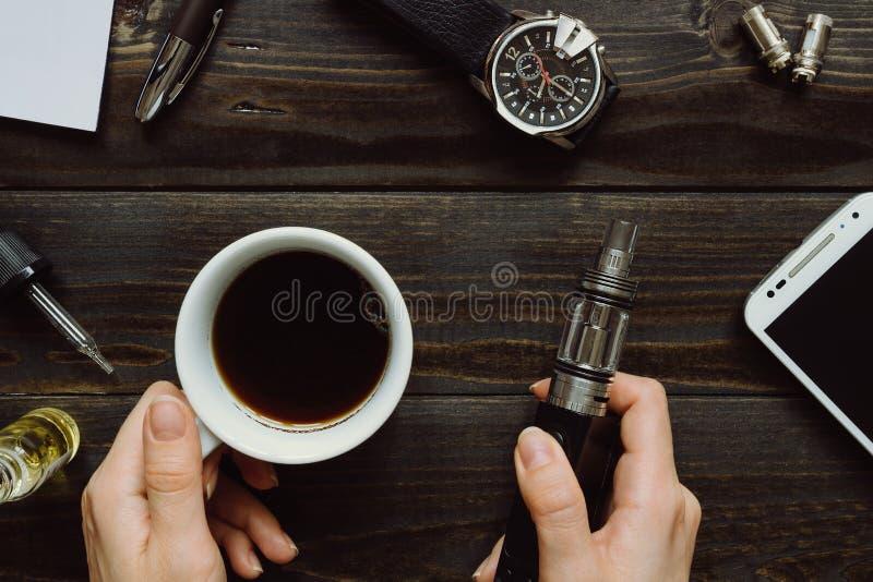 Ręki trzyma vape i kawę Vaping set, zegarek, smartphone dalej zdjęcia stock