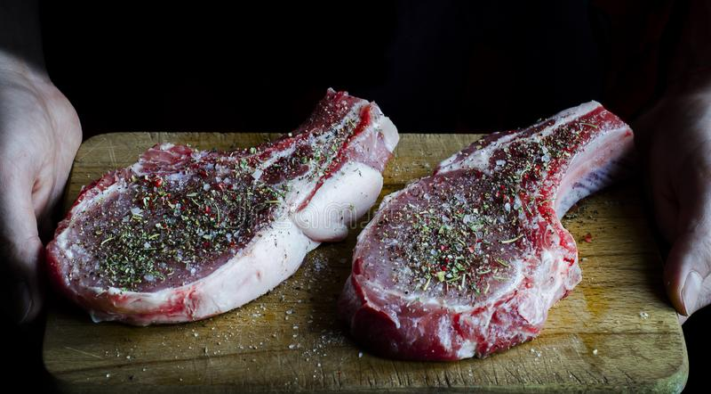 ręki trzymają deskę na którym przygotowywają gotować i są dwa surowego wieprzowina stku kropiącego z pikantność zdjęcie stock