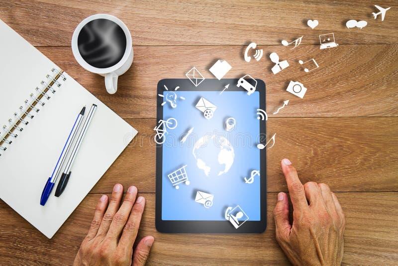 Ręki używać pastylka komputer z światową mapą, ikony, notatnik, pióra i gorąca filiżanka na drewnianym biurku, socjalny i biznesu fotografia stock