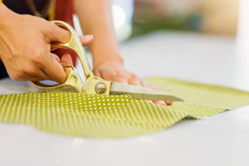 Ręki unrecognizable krawieckiej kobiety tnąca tkanina z nożycowym obrazy royalty free