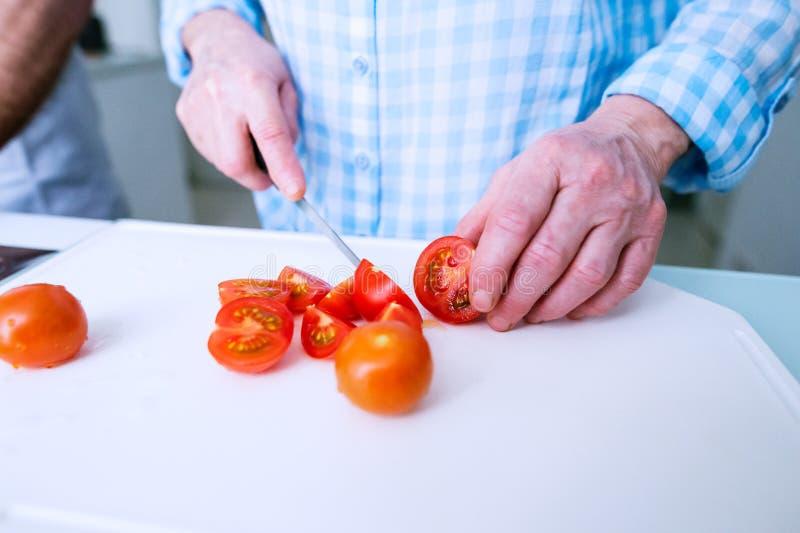 Ręki unrecognizable starszej kobiety tnący pomidory narządzanie zdjęcia stock