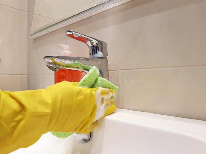 Ręki w żółtym rękawiczki obmycia gosposi zlew czyścą sanitarnego w ceramicznym łazienki obmyciu zdjęcie royalty free
