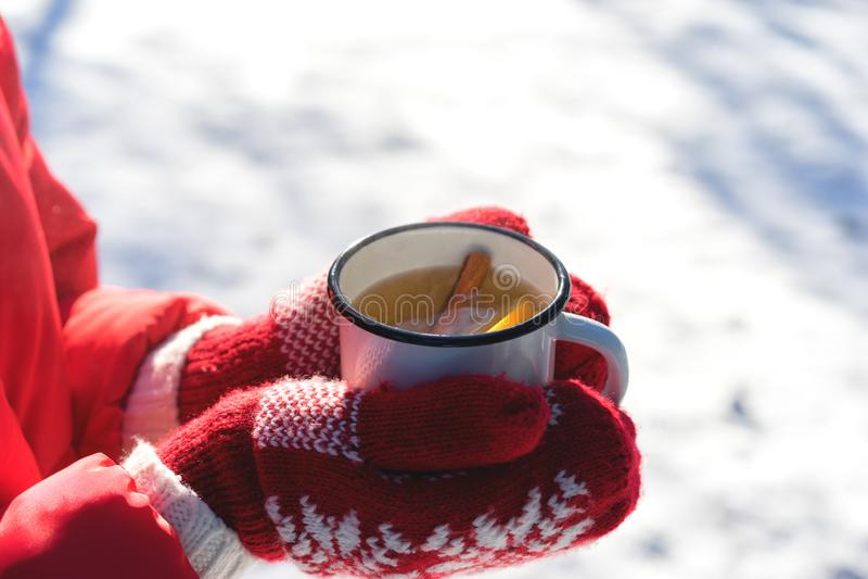 Ręki w Trykotowych mitynkach trzyma Parującą filiżankę Gorąca herbata na Śnieżnym zima ranku Outdoors Kobieta trzyma Wygodną Świą fotografia royalty free
