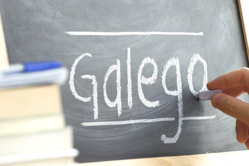 Ręki writing na blackboard w językowej klasie z słowem galicjanin napisał dalej fotografia stock