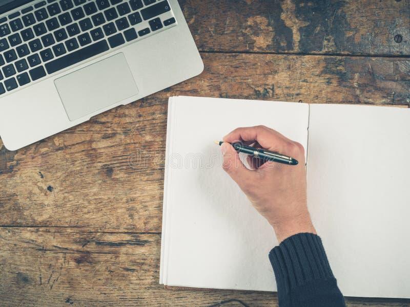 Ręki writing w notepad laptopem obraz stock