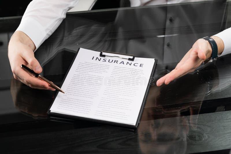 Ręki z piórem i ubezpieczeniem na stole fotografia stock