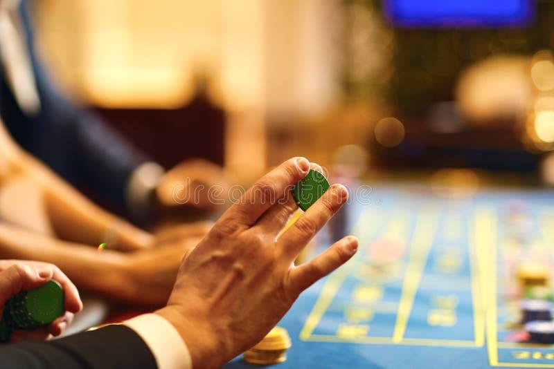 Ręki z układami scalonymi przy grzebak rulety stołowy uprawiać hazard w kasynie zdjęcie royalty free