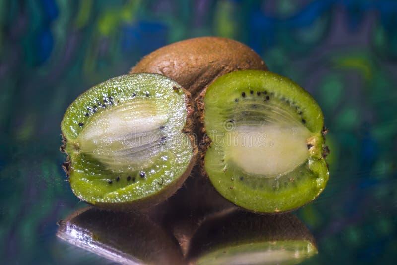 Rżnięty kiwi na lustrzanej powierzchni z abstrakcjonistycznym zieleni tłem zdjęcia royalty free