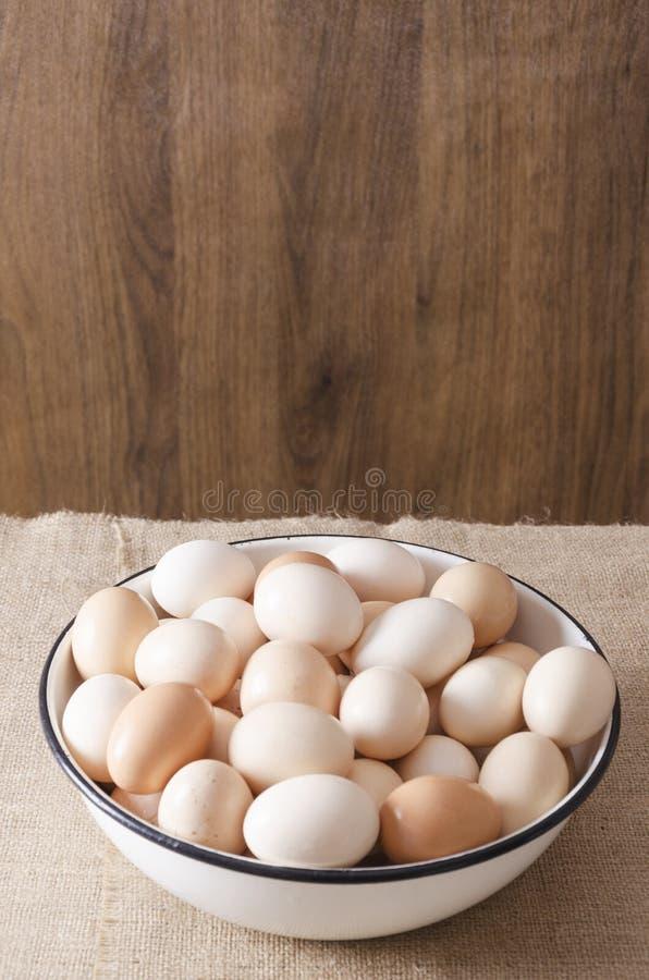r Ένα μεγάλο σύνολο κύπελλων των αυγών Μέρος των αυγών στο κύπελλο μετάλλων στο ξύλινο κλίμα Κενό διάστημα για το σχέδιό σας στοκ εικόνες
