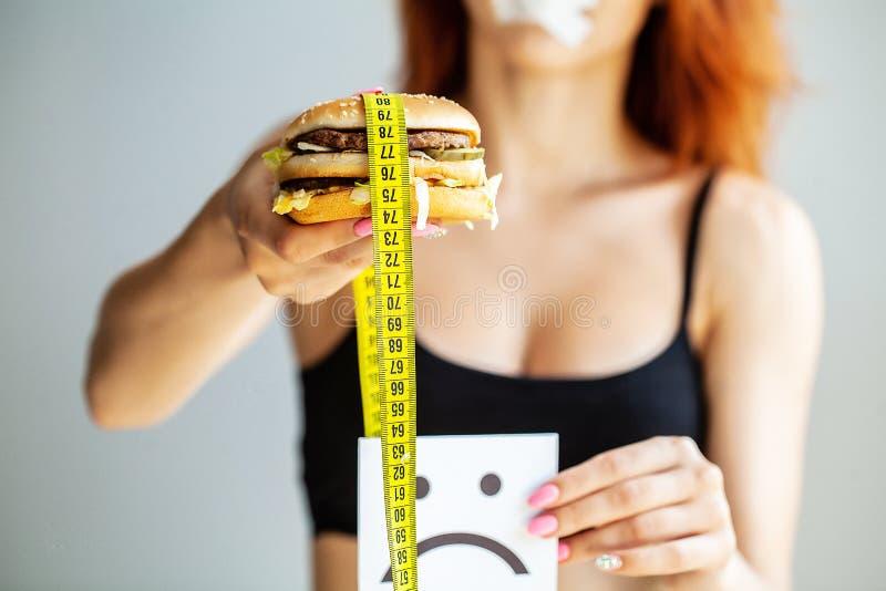 r Η γυναίκα πορτρέτου θέλει να φάει Burger αλλά το κολλημένο skochem στόμα, η έννοια της διατροφής, άχρηστο φαγητό, willpower μέσ στοκ φωτογραφία