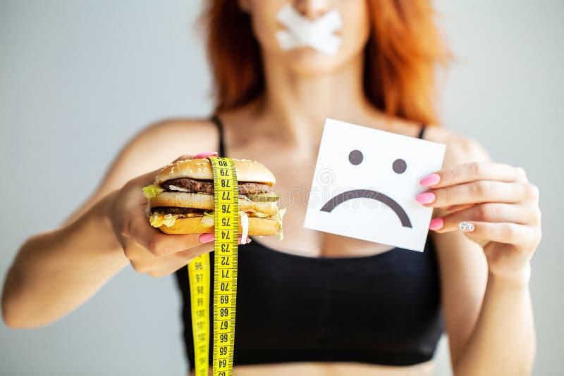 r Η γυναίκα πορτρέτου θέλει να φάει Burger αλλά το κολλημένο skochem στόμα, η έννοια της διατροφής, άχρηστο φαγητό, willpower μέσ στοκ φωτογραφία με δικαίωμα ελεύθερης χρήσης