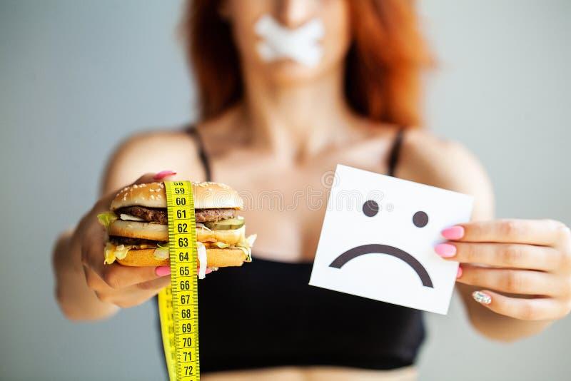 r Η γυναίκα πορτρέτου θέλει να φάει Burger αλλά το κολλημένο skochem στόμα, η έννοια της διατροφής, άχρηστο φαγητό, willpower μέσ στοκ εικόνες
