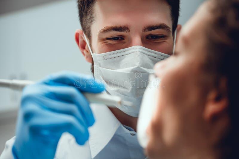 r Η εκλεκτική εστίαση των αρσενικών χεριών έφερε τα οδοντικά εργαλεία η σοβαρή αρσενική τοποθέτηση οδοντιάτρων στη μάσκα r στοκ φωτογραφίες με δικαίωμα ελεύθερης χρήσης