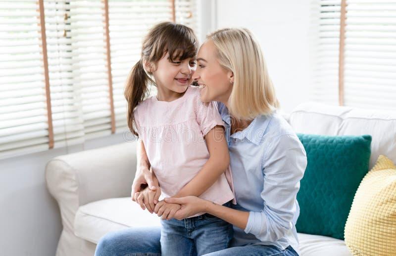 r Η μητέρα που αγκαλιάζει με την λίγη κόρη αγκαλιάζει και χαμογελά στο καθιστικό Άνθρωποι και οικογένεια και στοκ φωτογραφία με δικαίωμα ελεύθερης χρήσης