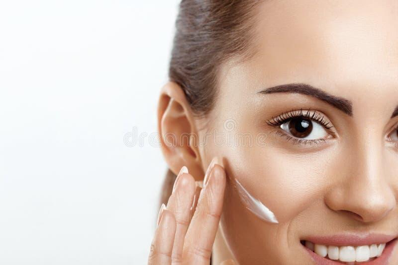 r Θηλυκό που εφαρμόζει την κρέμα και το χαμόγελο Πορτρέτο της νέας γυναίκας με την καλλυντική κρέμα στο δέρμα Κινηματογράφηση σε  στοκ εικόνα