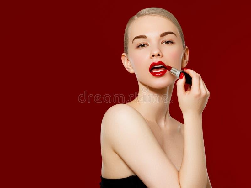 r Κινηματογράφηση σε πρώτο πλάνο του προσώπου γυναικών με το φωτεινό κόκκινο κραγιόν μεταλλινών στα πλήρη χείλια Καλλυντικά ομορφ στοκ φωτογραφία με δικαίωμα ελεύθερης χρήσης