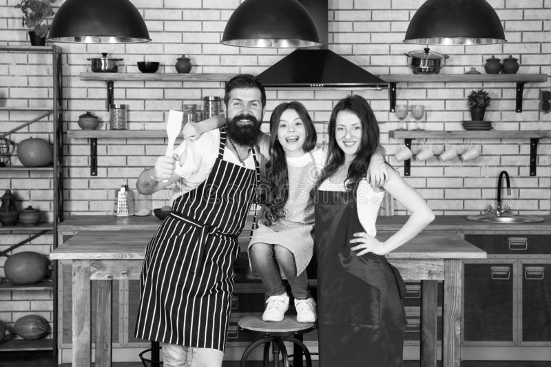 r Μητέρα και πατέρας με το μικρό κορίτσι Ευτυχής οικογένεια στην κουζίνα Μικρό κορίτσι με τους γονείς στην ποδιά Πατέρας στοκ εικόνα