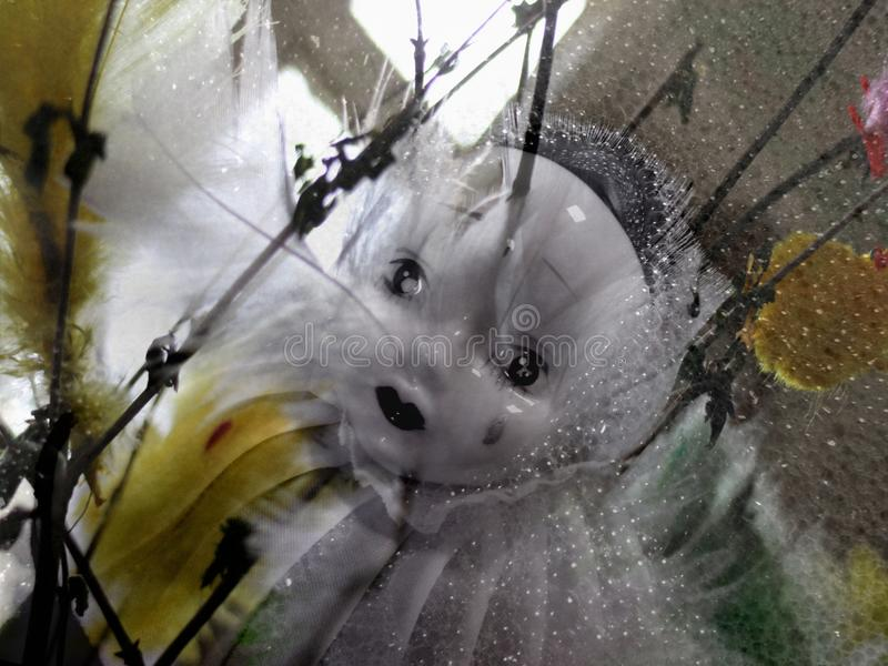 r Μια λυπημένη κούκλα πορσελάνης Pierrot μεταξύ των κλαδίσκων και των φτερών στοκ φωτογραφία με δικαίωμα ελεύθερης χρήσης