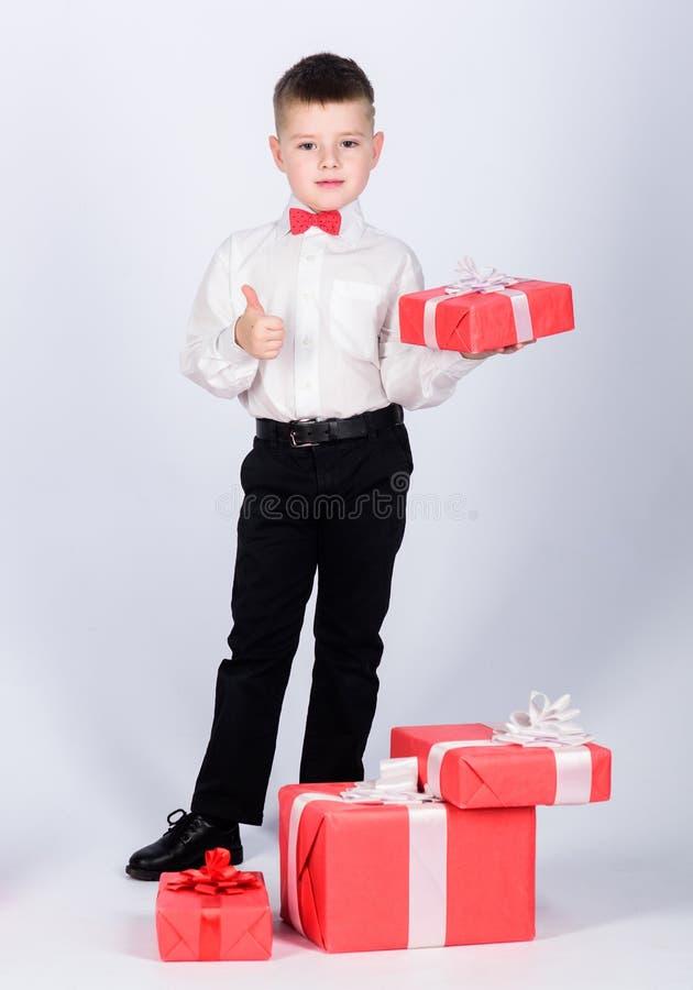 r μικρό παιδί με το δώρο ημέρας βαλεντίνων E Επόμενη μέρα των Χριστουγέννων Νέο έτος ύφος σμόκιν E στοκ εικόνα