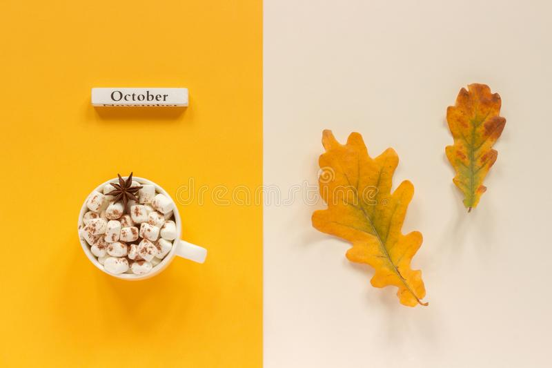 r Ξύλινος ημερολογιακός μήνας Οκτώβριος, φλυτζάνι του κακάου με marshmallows και τα φύλλα φθινοπώρου στο πορτοκαλί μπεζ υπόβαθρο στοκ φωτογραφία