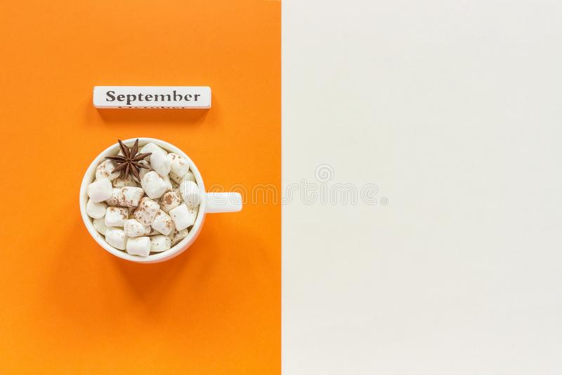 r Ξύλινος ημερολογιακός μήνας Σεπτέμβριος και φλυτζάνι του κακάου με marshmallows στο πορτοκαλί μπεζ υπόβαθρο r στοκ φωτογραφίες