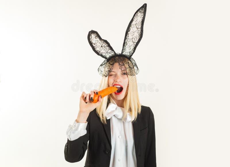 r Προκλητικό λαγουδάκι Πάσχας που τρώει το καρότο Αισθησιακή γυναίκα που φορά τα μαύρα αυτιά κουνελιών Πάσχας δαντελλών Πάσχα είν στοκ εικόνα
