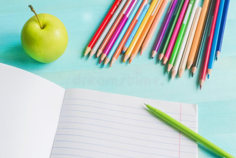 r Σχολικά εξαρτήματα, χρωματισμένα μολύβια, μάνδρα με το κενό σημειωματάριο στο μπλε ξύλινο υπόβαθρο στοκ φωτογραφία με δικαίωμα ελεύθερης χρήσης