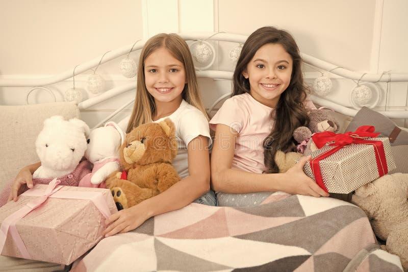 r Τα χαριτωμένα μικρά κορίτσια με παρουσιάζουν στο κρεβάτι Το άνοιγμα παρουσιάζει Νέα έκπληξη έτους r στοκ εικόνες