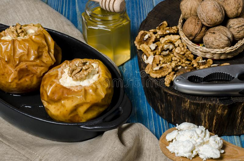 r Τα ψημένα μήλα με το τυρί εξοχικών σπιτιών και τα καρύδια βρίσκονται σε ένα μαύρο πιάτο ψησίματος σε έναν μπλε ξύλινο πίνακα στοκ φωτογραφίες με δικαίωμα ελεύθερης χρήσης