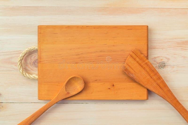 r Τοπ άποψη του κενοί ξύλινοι τέμνοντες πίνακα, του κουταλιού και spatula στον εκλεκτής ποιότητας πίνακα σανίδων με το διάστημα α στοκ φωτογραφίες