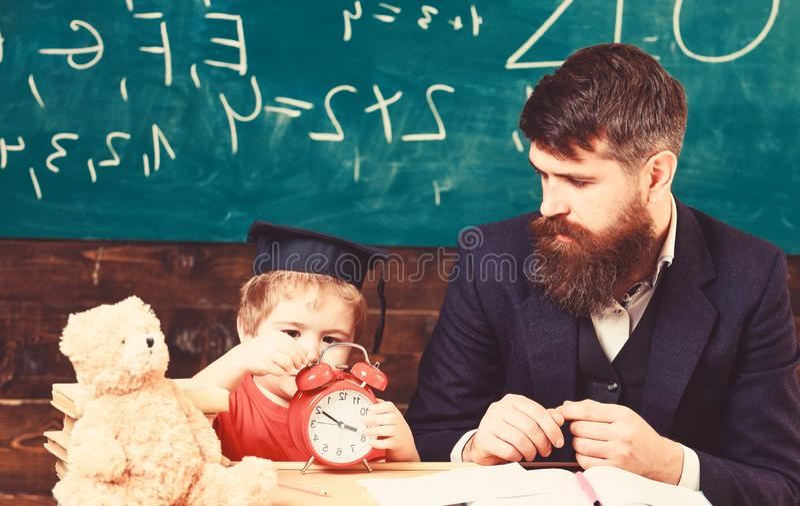 r Το αγόρι, παιδί στο ήρεμο πρόσωπο κρατά το ξυπνητήρι ενώ συζήτηση δασκάλων στο παιδί Δάσκαλος με τη γενειάδα στοκ φωτογραφίες με δικαίωμα ελεύθερης χρήσης